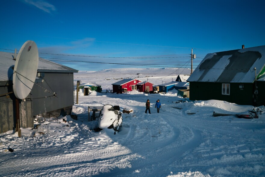People walk through Toksook Bay, an Alaskan fishing village along the Bering Sea.