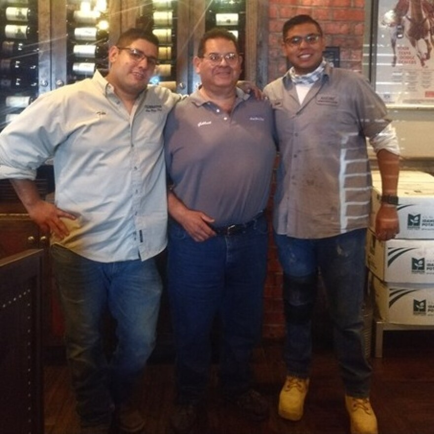 A family photo taken on Aug. 1 shows El Paso shooting victim Andre Anchondo (right) with his older brother Tito (left) and their father, Gilbert. The picture was taken at their father's auto body shop just two days before Andre Anchondo and his wife were killed by a gunman during a mass shooting in El Paso.