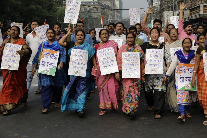 In Kolkata, protesters hold banners and shout slogans during a march against the decision to withdraw high denomination notes from circulation.