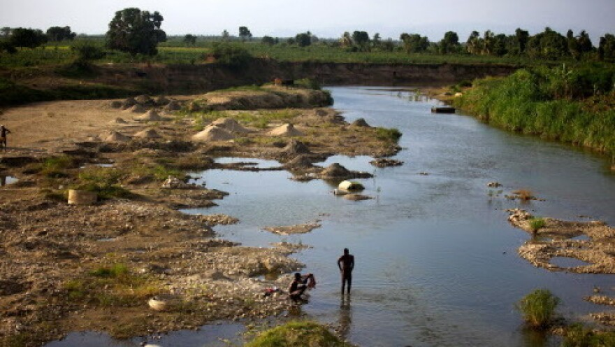 Men bathe in a branch of the Artibonite River outside Saint-Marc. Haiti's cholera outbreak in 2010 began about 60 miles upstream from here.