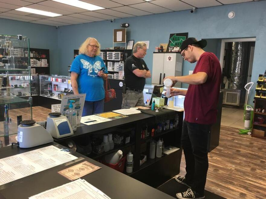 At All Ways Vapor: Sandy and Daniel Holloway look on while Chris Watford mixes the e-liquid they ordered. The Holloways turned to vaping as a way to quit smoking.