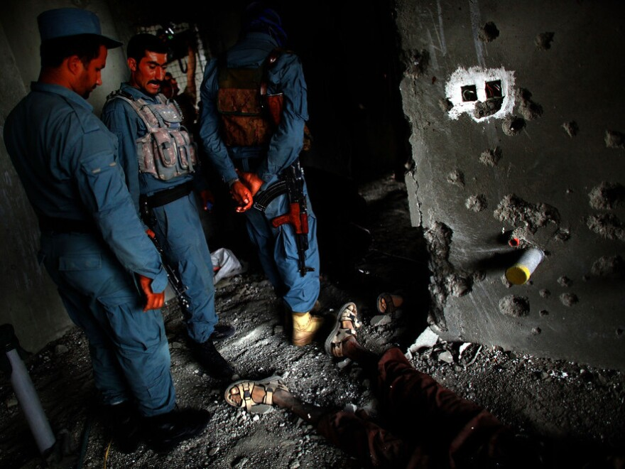 Sept. 13: Afghan Security personnel stand above the body of one attacker, on the 10th floor of the building in Kabul from which RPGs and other weapons were fired toward the U.S. embassy.