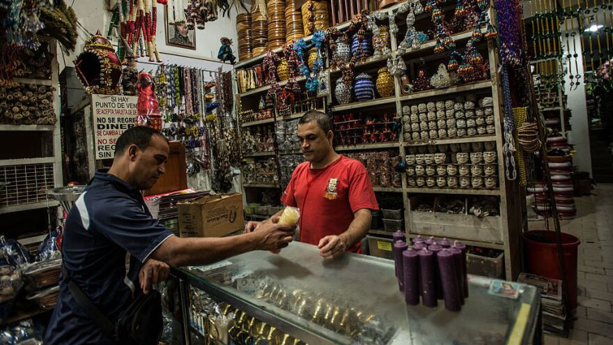 A customer buys candles for electricity rationing and Holy Week at a shop in central Caracas, Venezuela, in March.