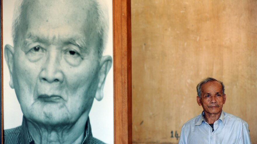 "A Cambodian survivor of the infamous Tuol Sleng prison (known as S-21) poses by a picture of ""Brother Number Two"" Nuon Chea last year."