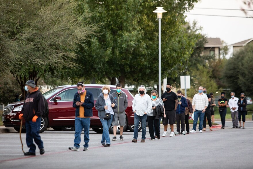 Voters line up on the first day of early voting at Southpark Meadows shopping center in South Austin.