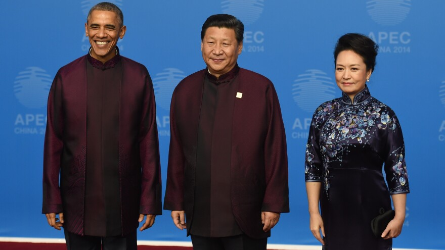 President Obama poses with Chinese President Xi Jinping and his wife, Peng Liyuan, as they arrive for the APEC banquet Monday. It's traditional for leaders attending the summit to dress alike for a photo op.