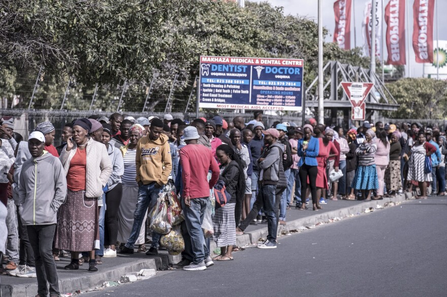 Shoppers line up for food outside a supermarket in the township of Khayelitsha in Cape Town during South Africa's lockdown.