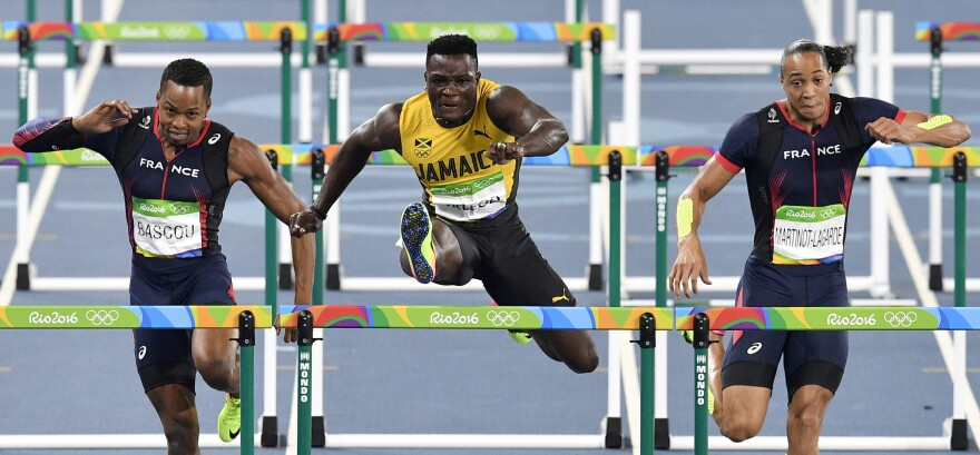 Jamaica's Omar McLeod (center) wins the 110-meter hurdles in Rio on Tuesday night. This was the third Jamaican sprint title already, and they are favored in more later this week.
