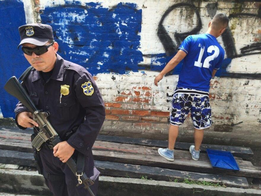 In Ciudad Delgado, a police officer guards a teen painting over gang tags. Conflicts between rival gangs are deadly, and hard for bystanders to avoid.