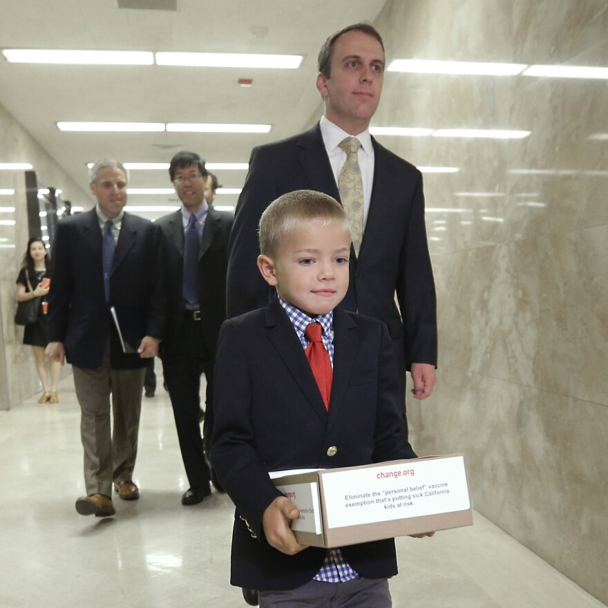 "Leukemia survivor Rhett Krawitt, 7, carries a box of petitions representing more than 30,000 people supporting a measure requiring nearly all California schoolchildren to be vaccinated. He took them to the governor's office at the Capitol in Sacramento, Calif., on Wednesday. The state Assembly voted Thursday to remove so-called ""personal belief exemptions"" for immunizations."