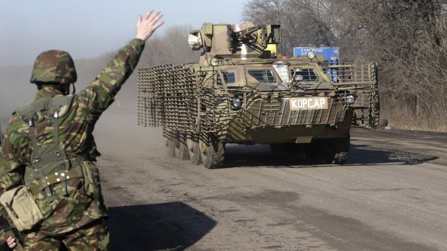 A Ukrainian government soldier waves to an armored vehicle on a road near the town of Artemivsk, Ukraine, Friday. Fighting between Russia-backed separatists and Ukrainian government forces has continued despite the agreement reached by leaders of Russia, Ukraine, Germany and France in the Belarusian capital of Minsk Thursday.