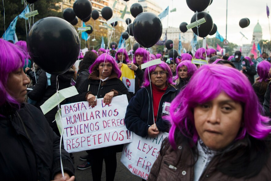 "Demonstrators wearing purple wigs representing the ""Ni Una Menos"" (Not One [Woman] Less) movement hold signs saying ""Enough humiliation, we have rights, respect us"" during a June 2016 protest against violence against women in Buenos Aires, Argentina."