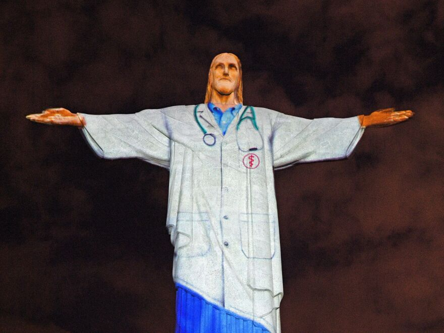 A doctor's white coat is projected onto the Christ the Redeemer statue in Rio de Janeiro, Brazil, on Easter Sunday, to honor medical workers who are fighting to save lives during the coronavirus pandemic.