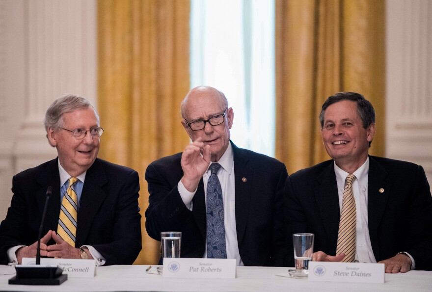 Steve Daines of Montana (right) talks with fellow Republican Sens. Mitch McConnell and Pat Roberts in a White House meeting in June on the GOP health care strategy, which would include deep cuts to Medicaid. Montana insurers say the plan worries them.