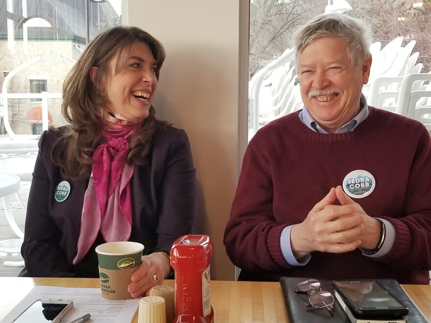 """New York House candidate Tedra Cobb visits with Gordon Miller and other Vermont residents at a cafe in Burlington, Vt. """"We can't vote,"""" Miller said of the New York race, """"but certainly we can provide financial support."""""""