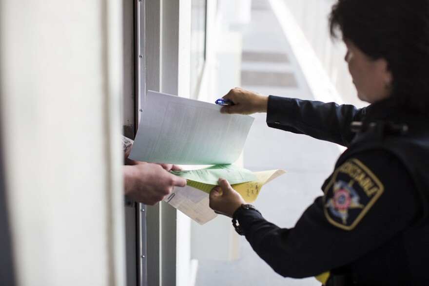 Travis County Deputy Theresa Stewart serves an eviction suit to a tenant in Southwest Austin in 2018.