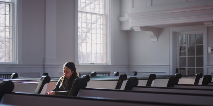 Photo of Vicki Chavez sitting in a pew in an empty sanctuary.
