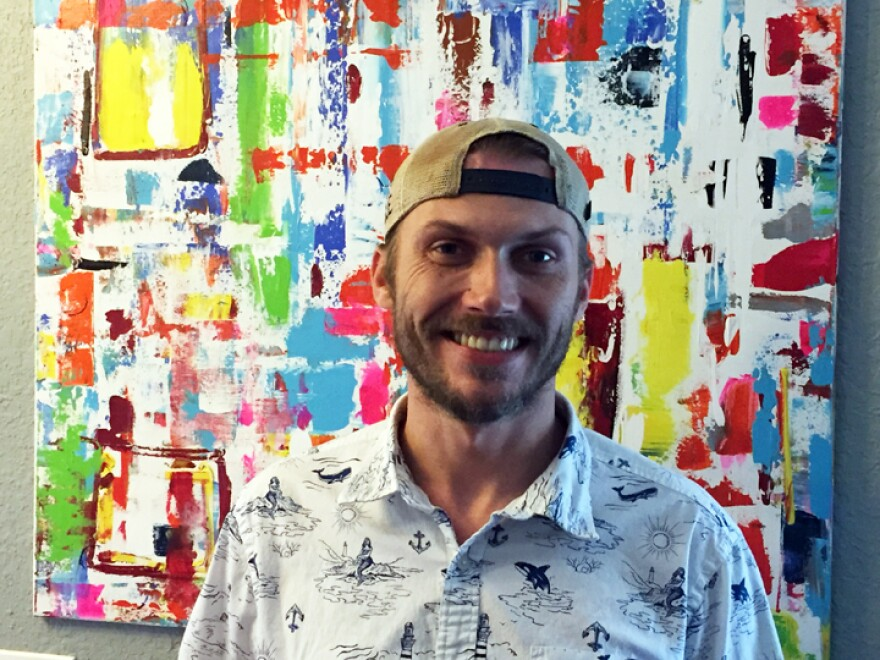 Charles Claybaker photographed in front of artwork that he painted as part of his therapy.