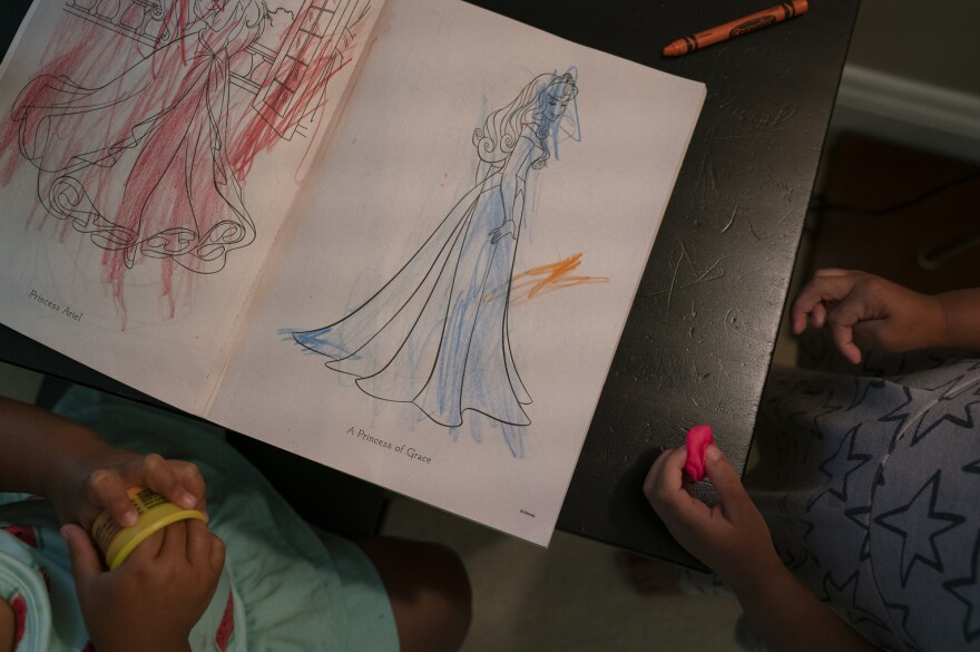 After the migrant children come home from school, they work on a princess coloring book.