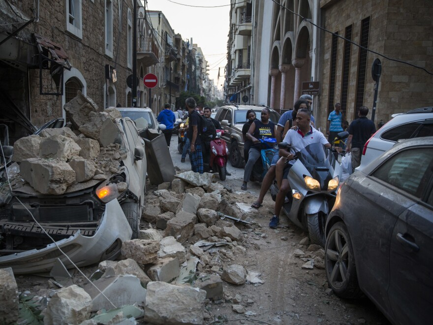 People move past a car destroyed after a building wall collapsed due to a large explosion in Beirut, Lebanon, Tuesday. Video shared on social media showed an enormous explosion followed a smaller fire in the area of Beirut's port. Thousands of people were wounded.
