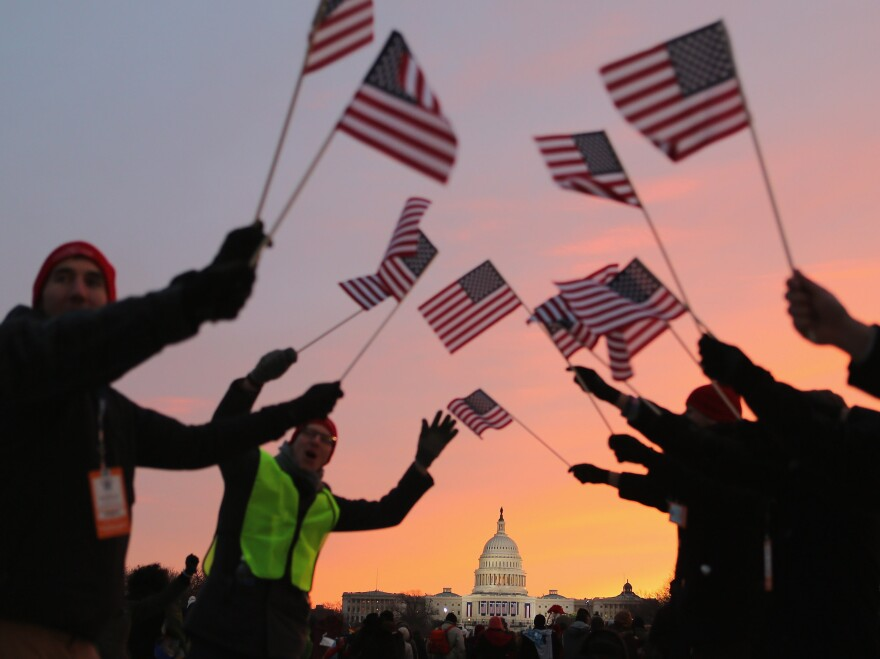 People wave American flags as they gather on the National Mall for the inauguration ceremony Monday.