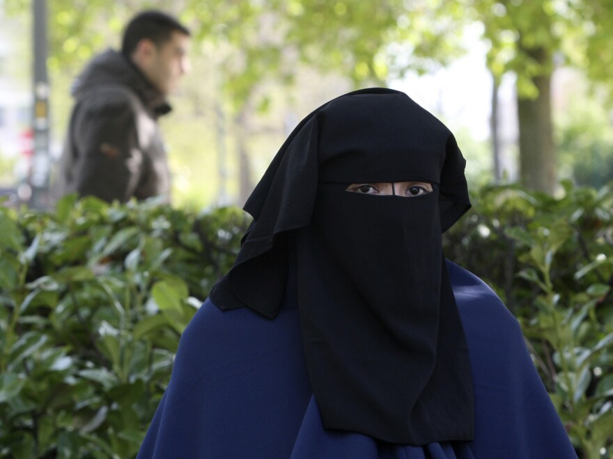 A young woman wears the niqab, or full face veil, as she sits in a park in Brussels in 2010. On Tuesday, the European Court of Human Rights upheld Belgium's 2011 ban on wearing partial or full face veils in public.