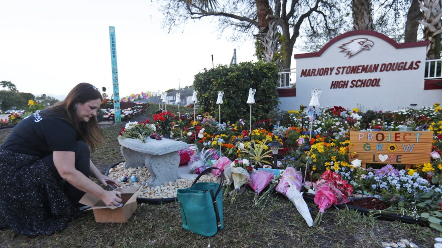 Suzanne Devine Clark, an art teacher at Deerfield Beach Elementary School, places painted stones at a memorial outside Marjory Stoneman Douglas High School on the first anniversary of the school shooting Thursday.