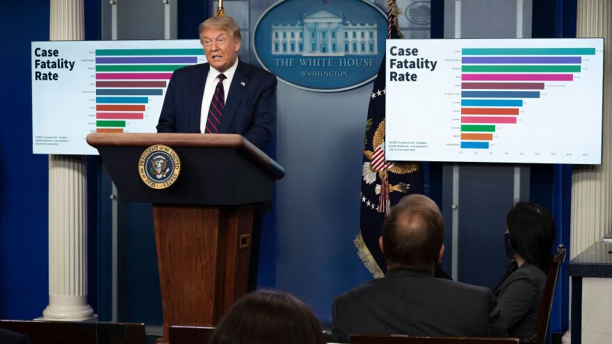 President Trump speaks during a briefing Tuesday at the White House with a chart showing case fatality rate behind him.