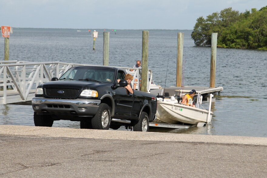 A truck loads a boat into the water at Anclote River Park.