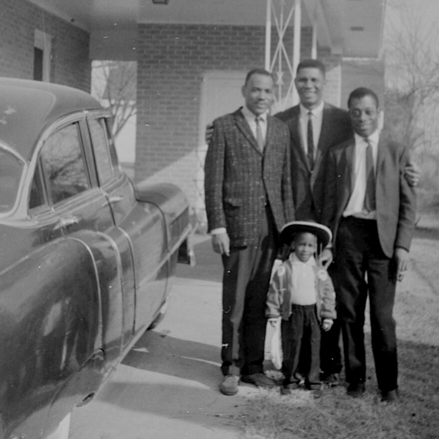 """Medgar Evers embraces friends James Meredith (left), the first black student to enroll in the University of Mississippi (with Evers' help), and iconic writer James Baldwin (right), who covered the civil rights movement for magazines like <em>The New Yorker</em>. Van Evers stands in front: """"It's one of the very few photos I have of my dad and me,"""" he says."""
