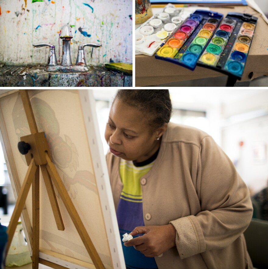 """A paint-splattered sink and open watercolor palette show signs of art in progress at Art Enables, a studio for people with disabilities that was founded in 2001. Artist Vanessa Monroe, who has been interested in art since childhood, concentrates as she paints a canvas at Art Enables. """"We're just like family,"""" she says about being part of the studio."""