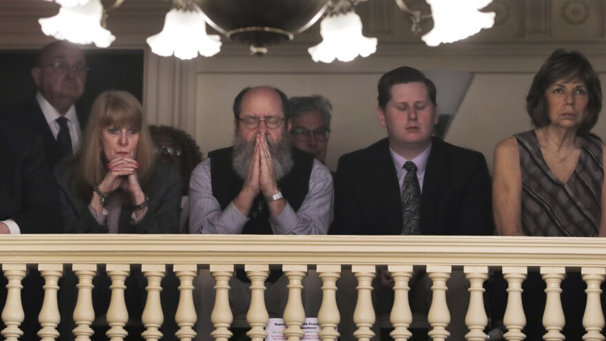 Rob Spencer prays as New Hampshire lawmakers debate prior to a death penalty vote at the State House in Concord, N.H., on Thursday. The legislature abolished capital punishment by overriding a veto by Gov. Chris Sununu.