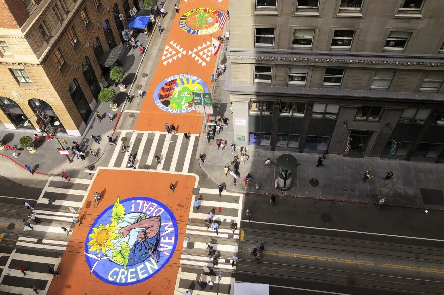 Murals painted by climate activists are seen from an office building on Montgomery Street in San Francisco on Sept. 25.