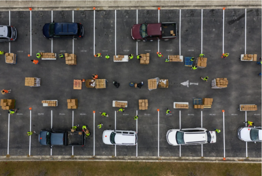 An overhead shot of a line of cars winding its way around a group of food bank workers distributing food in a parking lot.