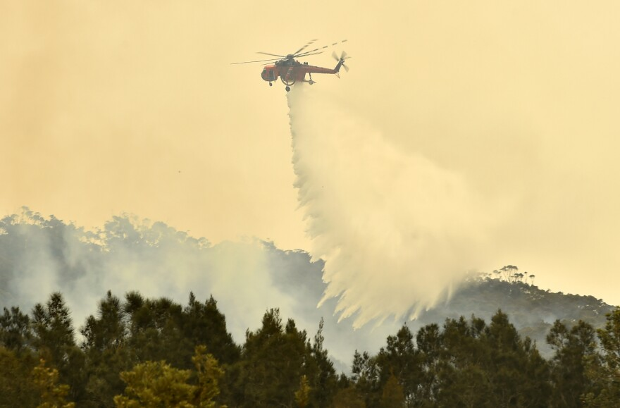 A helicopter drops water on a bushfire outside of Batemans Bay in New South Wales on Thursday.