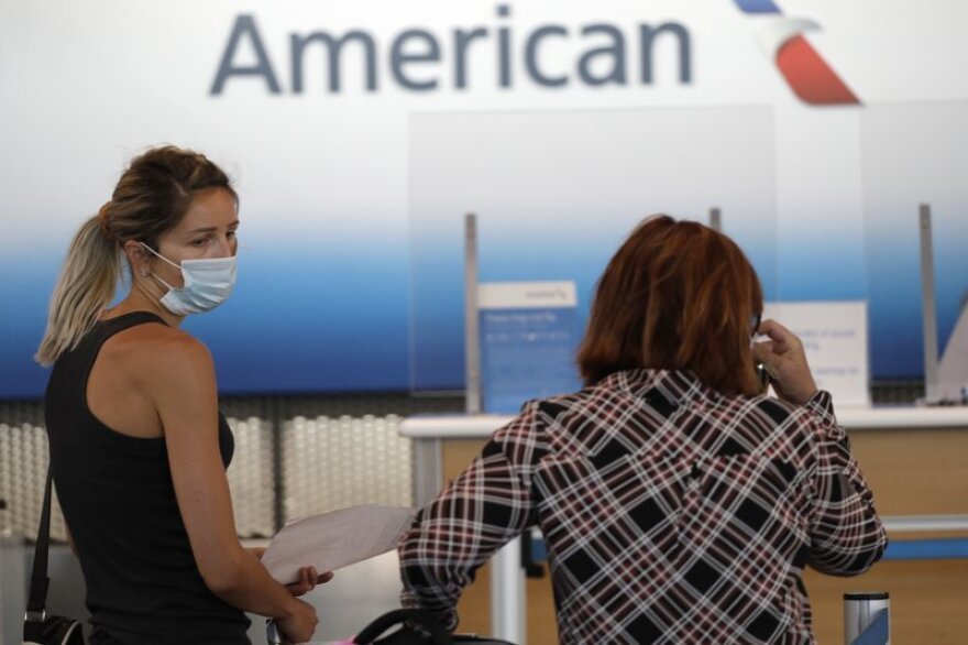 Travelers wear masks as they wait at the American Airlines ticket counter at O'Hare International Airport in Chicago.