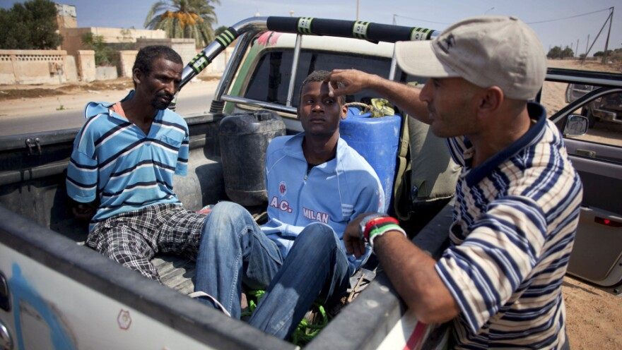 <p>A revolutionary fighter watches over two suspected Gadhafi loyalists in Sirte, Libya, last month. By some estimates, up to 30 to 40 percent of Libyans are sympathetic to former dictator Moammar Gadhafi.</p>