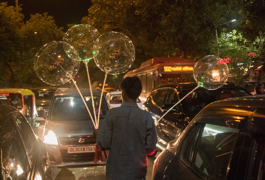 Radhesham Singh, a homeless 28-year-old street vendor in New Delhi, saunters amid traffic, selling balloons.