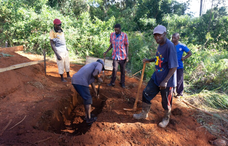 Gravediggers prepare the burial  site for 3-year-old Excite, who died after the cyclone hit.