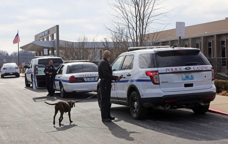 Police officers stand by as adults and children return to the St. Louis Jewish Community Center in St. Louis after canine units cleared the building Wednesday. According to St. Louis County Police, someone called the front desk claiming an explosive device was inside the center.