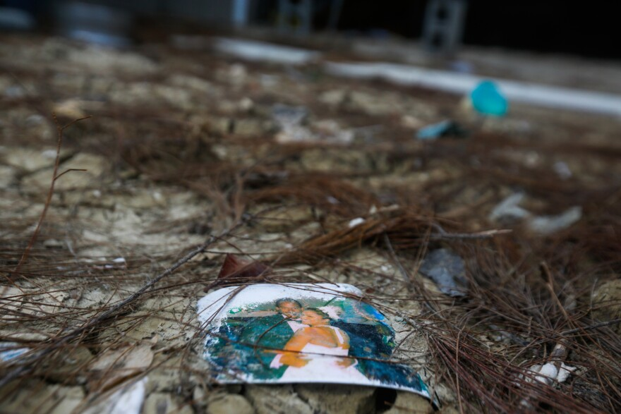 "A wedding photo rests in the dirt outside of Geno Daniels' home in the Queen's Cove neighborhood of Freeport, Grand Bahama on September 17, 2019.  ""It's sad to watch this all go down the drain,"" he said."