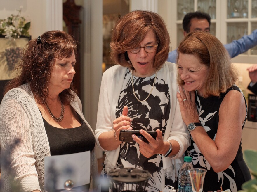 Marilyn Geewax talks with former classmates Marcia Stanton (left) and Mary Ann Brayer during a pre-reunion party at a home in Poland, Ohio, in July.
