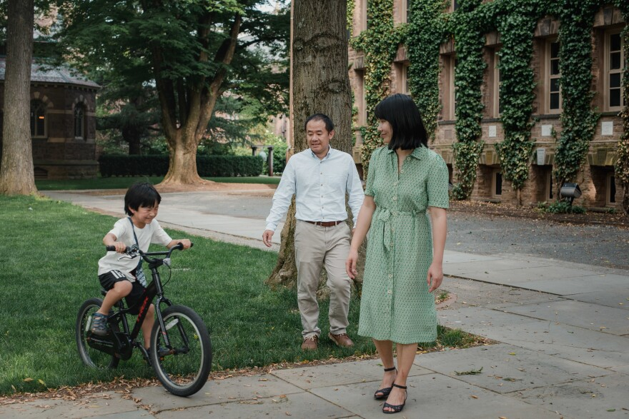 Wang and Qu watch as their 7-year-old son rides his bike around Princeton University in Princeton, N.J. When Wang left for Iran, their son was 3 years old.