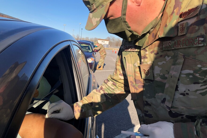 At a drive-through vaccination site in Elizabeth City, N.C., Tech Sgt. Steven Simpson of the North Carolina National Guard administers a COVID-19 vaccination as Maj. Hollis Guenther gives the next recipient instructions about the vaccine.