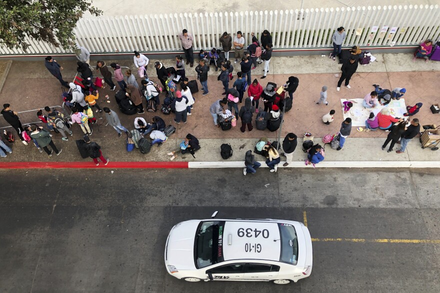 In this Nov. 10, 2019, photo, migrants gather at the U.S.-Mexico border in Tijuana, Mexico, to hear names called from a waiting list to claim asylum in the U.S.