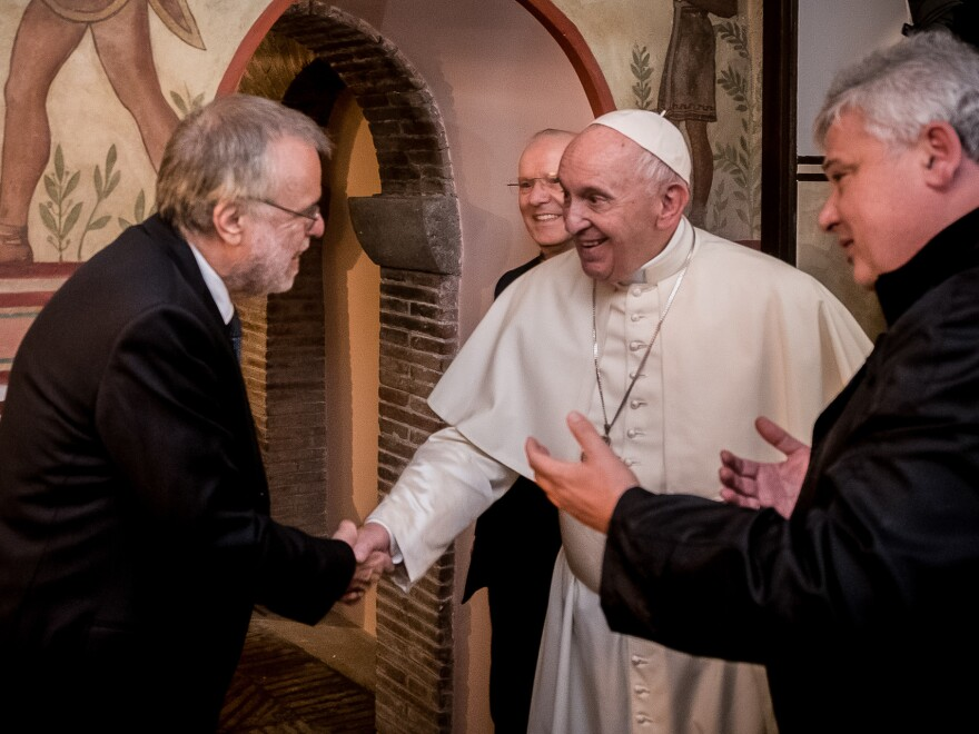 The pope shakes hands with Andrea Ricciardi, the founder of the Community of Sant'Egidio, the lay Roman Catholic group whose volunteers run the new homeless shelter.