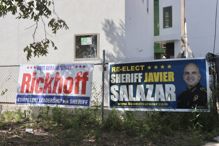 "Two campaign signs hang on a fence outside of a building. The left reads, ""Vote Gerard 'Gerry' Rickhoff Competent Leadership For Sheriff."" The right reads, ""Re-elect Sheriff Javier Salazar."""
