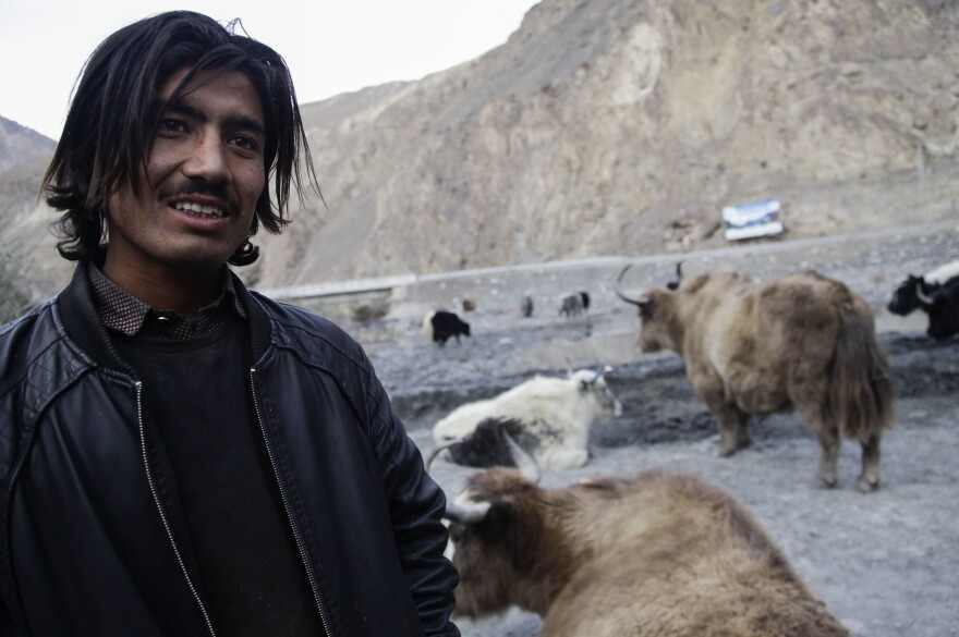 Suhail Abbas, 23, stands with his cabinet of yaks on the Karakoram Highway. He says since the road was resurfaced several years ago, his fortunes brightened as resident have more money to spend on things like yak meat.
