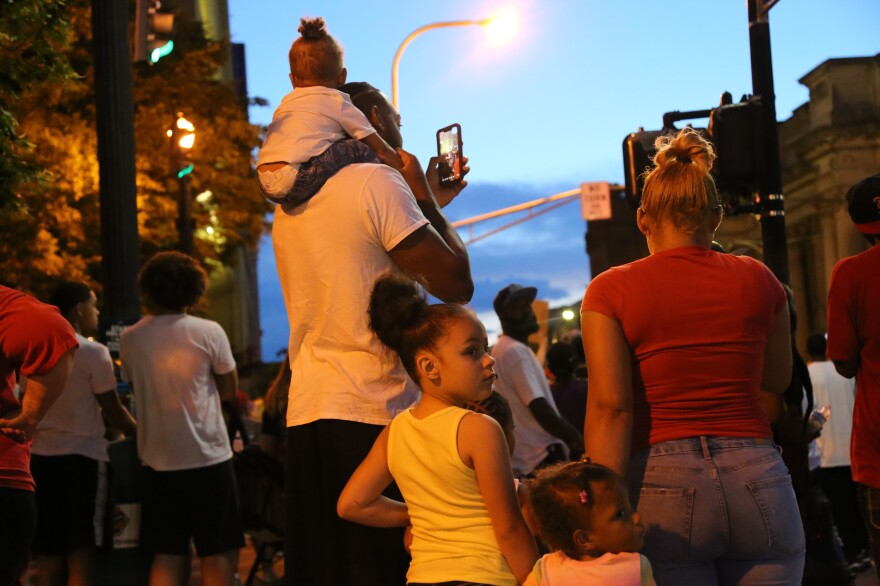 A family watches as protesters lock arms across a main thoroughfare in downtown Louisville Thursday, May 28, 2020.