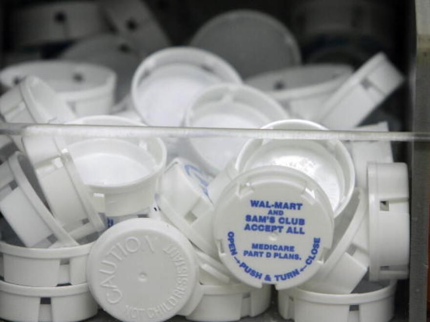 Tops to prescription bottles are pictured inside the Wal-Mart pharmacy.